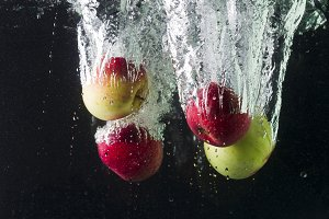 Apples in water on a black background