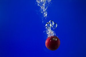 Apple in water on a blue background