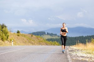Young slim woman in sportswear jogging on the road