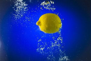 Yellow Lemon floating in the water on a blue background