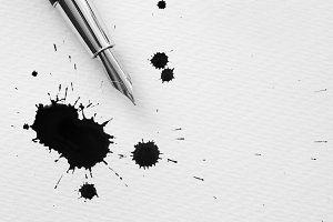 Pen and inkdrops on a paper