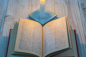 open book illuminated by a candle