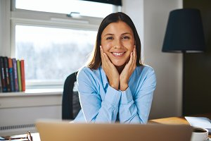 Happy young businesswoman working from home