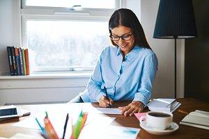 Cheerful woman writing checks at desk