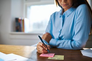 Close up of person writing on sticky notes