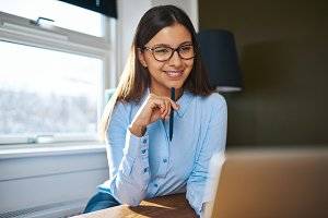 Positive self-employed woman working near window