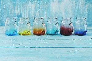 colored glass jars with handles on a wooden blue background