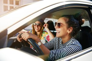 Laughing young girlfriends traveling in a car