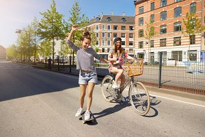 Cute friends on bike and skateboard in city