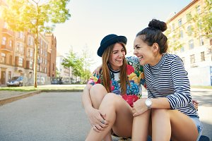 Two young women sitting laughing and joking