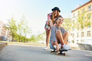 Happy young woman pushing friend on skateboard