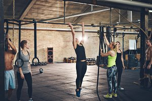 Adults doing pull ups on bar in gym