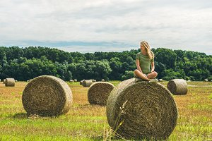 Girl sitting on haystack