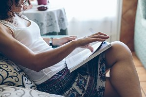 Young woman reading book on home