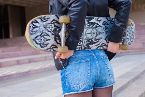 girl holding her skateboard
