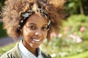 Happy stylish African girl with curly hair enjoying sunny weather in urban garden, breathing fresh air, looking at camera with joyful and pleased smile. Young woman resting outdoors on sunny day