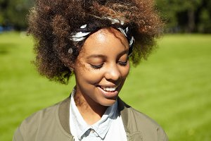 Outdoor portrait of good-looking young African female with curly hair, having nice time walking in city park. Beautiful girl with charming shy smile, closing her eyes because of bright sunshine