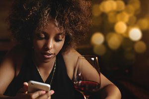 Chic dark-skinned female with Afro haircut, chilling at bar, drinking red wine, sitting at counter, holding mobile phone, texting friends via social networks. African girl typing message at night club