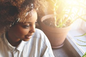 Flare sun. Young beautiful hipster student girl with Afro haircut, dressed in trendy clothes, sitting at home, looking through window at street with pensive expression before going to university