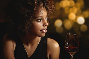Profile of beautiful African woman with stylish curlly hair wearing elegant black dress, enjoying red wine, siting at restaurant, having romantic dinner with husband, celebrating wedding anniversary