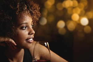 Half-profile portrait of black elegant female looking away in front of glass with red wine, thinking about something pleasant, half-smiling, isolated against blurred background of nightclub or bar