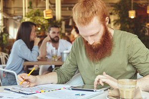 Young trendy entrepreneur with long red hair and beard working on prospective business plan sitting at coffee shop, reading something at pad, filling in charts on sheet of paper with another hand