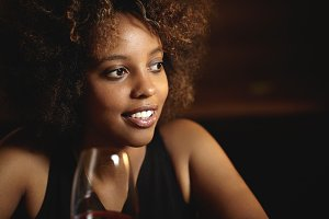 People and leisure. Elegant African woman with perfect tanned skin sitting at restaurant, holding glass of red wine, looking pensive and mysterious. Attractive female spending nice time at bar