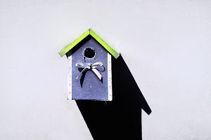 Birdhouse on a clean white wall