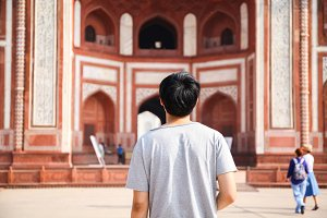Young traveler walking towards entrance to Taj Mahal in Agra, India.