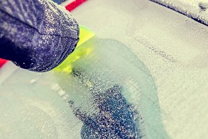Scraping ice from car window