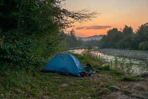 Camping by the river at sunrise