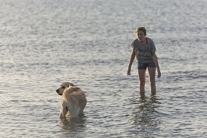 girl in the water with his dog
