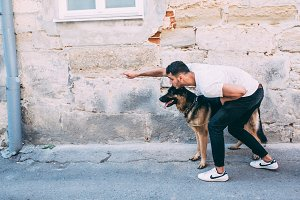 man and dog posing on the street