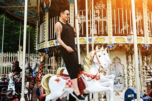 woman sitting at horse on a carousel