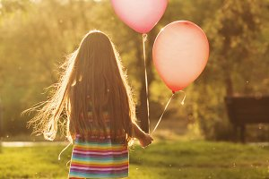 Little girl walking with balloons