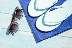 stylish sunglasses with flip flops and towel