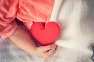 Baby hold love red heart