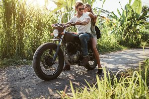 Young couple straddling motorbike