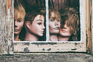 Ragged mannequin heads in window