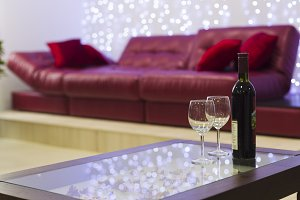 Interior with a coffee table, a sofa and a bottle of wine