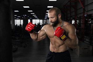 Strong muscular man boxing at the gym.