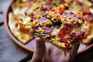 hand holding slice pizza