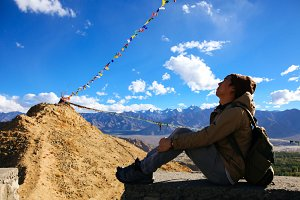 Young traveler sitting in the shade on the cliff over mountain of colorful prayer flags in Leh, Ladakh, India (Subject in the shadow tone)