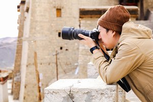 Travel photographer journalist holding a camera in mountain and ancient site background