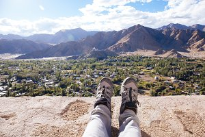 Traveler's boots relaxing and resting his feet on high mountain trekking and ancient town scene and adventure