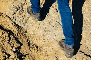 Close-up of traveler's feet walking uphill on mountain and sand dune - travel, vacation,recreation and adventure concept