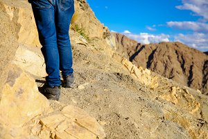 Close-up of traveler's feet walking uphill on mountain and sand dune over blue sky - travel, vacation,recreation and adventure concept