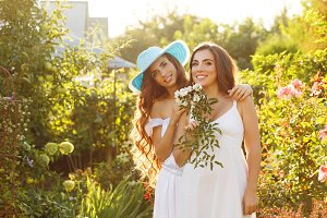 Two sisters with flowers in garden.