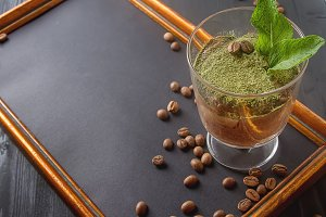 Traditional Italian cuisine. Chocolate tiramisu dessert with tea matcha. Coffee beans. Board for records, black wooden background.