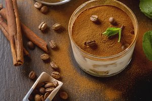 Traditional Italian cuisine. Dessert chocolate tiramisu, mint. Coffee beans. Black wood background.